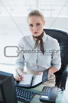 Blonde serious businesswoman writing in diary