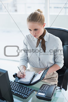 Blonde stern businesswoman writing in diary