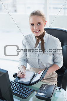 Blonde happy businesswoman writing in diary