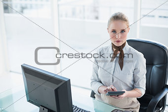 Blonde serious businesswoman using calculator