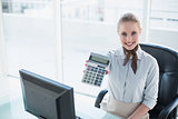 Blonde smiling businesswoman showing calculator