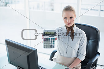 Blonde serious businesswoman showing calculator