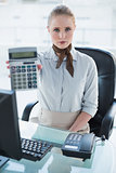 Blonde stern businesswoman showing calculator