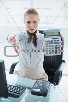 Blonde stern businesswoman showing calculator and thumb down