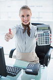 Blonde smiling businesswoman showing calculator and thumb up