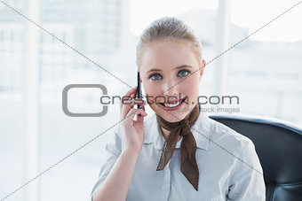 Blonde smiling businesswoman phoning