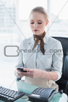 Blonde stern businesswoman using smartphone