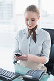 Blonde smiling businesswoman using smartphone