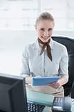 Blonde smiling businesswoman using tablet
