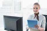Blonde happy businesswoman using tablet