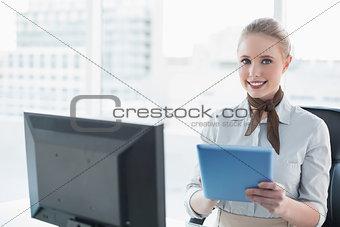 Blonde happy businesswoman using tablet