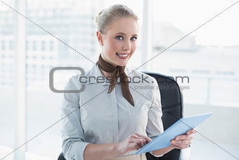 Blonde cheerful businesswoman using tablet