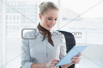 Blonde cheerful businesswoman looking at tablet