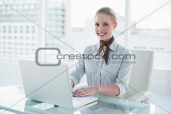 Blonde smiling businesswoman using laptop