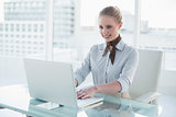 Blonde content businesswoman using laptop