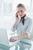 Blonde serious businesswoman using laptop and phoning