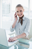 Blonde smiling businesswoman using laptop and phoning