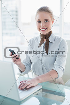 Blonde content businesswoman using laptop and smartphone