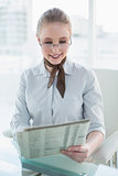 Blonde smiling businesswoman reading newspaper