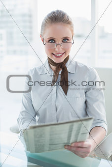 Blonde smiling businesswoman holding newspaper