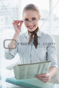 Blonde cheerful businesswoman holding newspaper