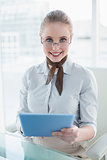 Blonde content businesswoman holding tablet