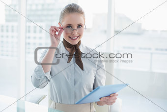Blonde laughing businesswoman holding tablet