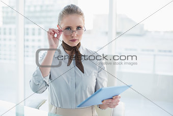 Blonde frowning businesswoman holding tablet