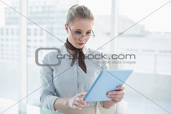 Blonde stern businesswoman looking at tablet