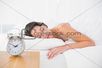 Peaceful casual brunette in white pajamas sleeping in her bed