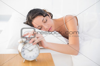 Sleepy casual brunette in white pajamas turning off her alarm clock