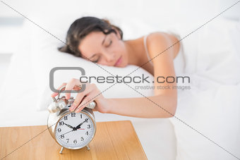 Calm casual brunette in white pajamas turning off her alarm clock