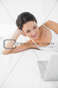 Relaxed casual brunette in white pajamas looking at a laptop
