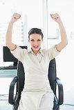 Cheering stylish brunette businesswoman raising her arms
