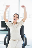 Excited stylish brunette businesswoman raising her arms