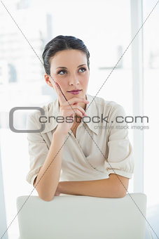 Thoughtful stylish brunette businesswoman posing looking away