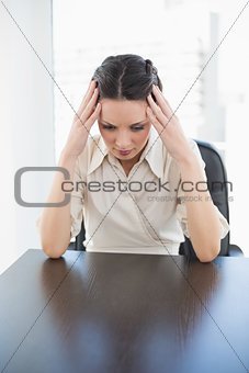Nervous stylish brunette businesswoman holding her head