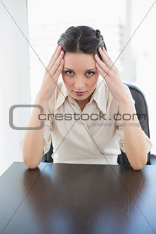 Worried stylish brunette businesswoman holding her head