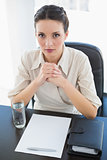 Stern stylish brunette businesswoman joining her hands and looking at camera