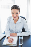 Cute stylish brunette businesswoman taking notes and looking at camera