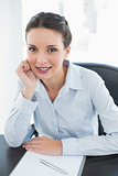 Cheerful stylish brunette businesswoman holding her head and looking at camera