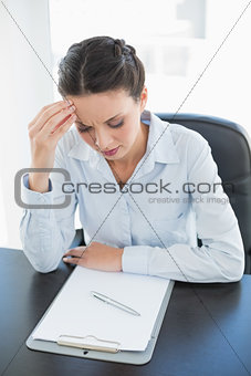 Focused stylish brunette businesswoman looking at her clipboard