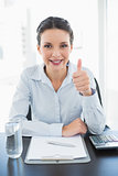 Pleased stylish brunette businesswoman giving thumb up