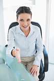 Content stylish brunette businesswoman presenting her hand