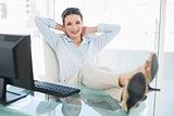 Content stylish brunette businesswoman relaxing with feet up