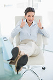 Cheerful stylish brunette businesswoman relaxing with feet up and giving thumbs up