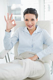 Content stylish brunette businesswoman making an okay gesture