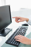 Close up of a businesswoman pointing to her computer screen with her finger