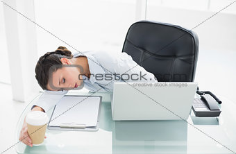 Tired stylish brunette businesswoman sleeping on her desk