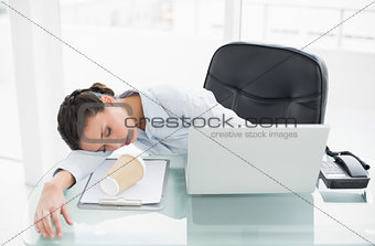Sleepy stylish brunette businesswoman lying on her desk